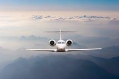 L'aeroplano sorvola le nuvole e la montagna delle alpi sul tramonto Vista frontale di grande aereo del carico o del passeggero, a fotografie stock