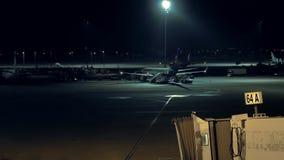 L'aeroplano sta stando fermo all'aeroporto alla notte stock footage