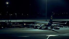 L'aeroplano sta stando fermo all'aeroporto alla notte video d archivio