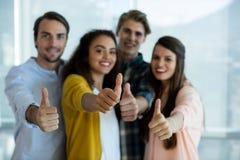 L'affare creativo sorridente team mostrando i pollici su nell'ufficio Fotografie Stock Libere da Diritti