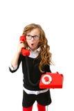 L'affare ha sorpreso la bambina con un telefono rosso su un backg bianco Fotografie Stock Libere da Diritti