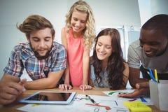 L'affare sorridente team facendo uso della compressa digitale allo scrittorio Fotografie Stock