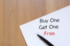 L'affare uno ottiene uno libero scrive sul taccuino Immagine Stock