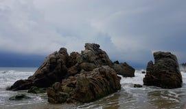 L'affioramento roccioso sulla spiaggia come nuvole arriva a fiumi Immagine Stock