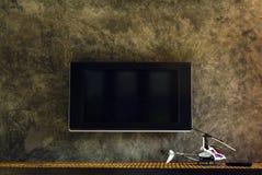 L'affissione a cristalli liquidi TV ha montato davanti alla parete del cemento Fotografia Stock