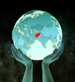 L'Afghanistan sur le globe bleu dans des mains Illustration Libre de Droits
