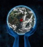 L'Afghanistan sur terre de planète de nuit dans des mains Illustration Stock