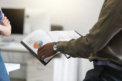 L'Afro-américain équipe des mains tenant le document dans un bureau Images libres de droits