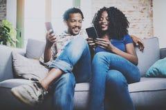 L'afro-américain de sourire couplent la détente ensemble sur le sofa Jeune homme de couleur et son amie à l'aide des smartphones  Image stock