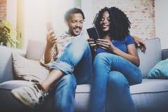 L'afro-américain de sourire couplent la détente ensemble sur le sofa Jeune homme de couleur et son amie à l'aide des smartphones  Images libres de droits