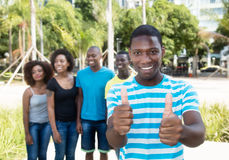 L'afro-américain riant équipent montrer le pouce avec le groupe de personnes Image libre de droits