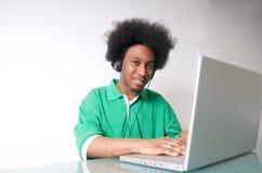 L'afroamericano ascolta musica con il computer portatile Immagini Stock Libere da Diritti