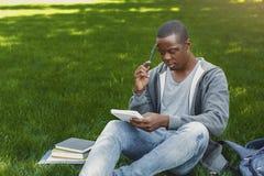L'afroamericano concentrato studen la seduta con il taccuino sull'erba Immagini Stock Libere da Diritti