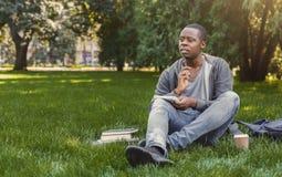 L'afroamericano concentrato studen la seduta con il taccuino sull'erba Immagine Stock