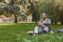 L'afroamericano felice studen la seduta con il taccuino sull'erba Immagini Stock Libere da Diritti