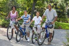 L'afroamericano Parents i bambini del ragazzo che guidano le bici Fotografia Stock