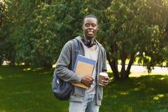 L'afroamericano studen con i libri in parco all'aperto Immagine Stock