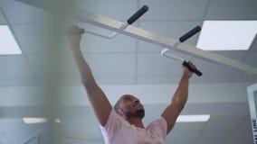 L'afroamericano tira su sulla barra orizzontale nella gente della palestra nello stile di vita sano della palestra stock footage