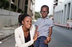L'agenouillement de jeune femme prend une photo avec son enfant Photos stock