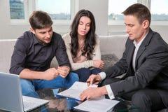 L'agent conseille les couples, signant des documents photos stock