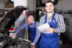 L'agent d'assurance et le mécanicien calculent la perte Images stock