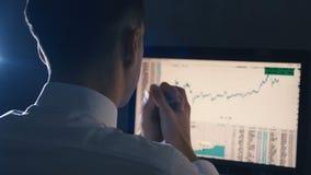 L'agent de change travaille sur la stratégie d'analyse marchande financière globale de croissance à l'ordinateur banque de vidéos
