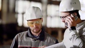 L'agent de maîtrise et l'architecte dans les casques de protection appellent le client au téléphone portable au client de projet  clips vidéos