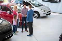 L'agent de voiture félicitent la famille sur la voiture de achat Photos libres de droits