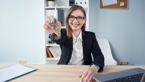 L'agent immobilier de femme donne les clés à un appartement aux clients banque de vidéos