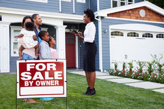 L'agent immobilier et la famille en dehors de la maison avec un ½ de ¿ d'ï pour le ½ de ¿ de saleï signent images libres de droits