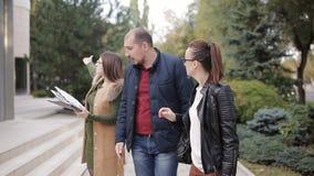 L'agent immobilier et le jeune progulyatsya de couples l'allée et discutent le bail ou l'achat d'une nouvelle maison clips vidéos