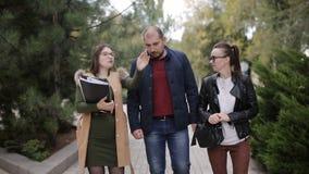 L'agent immobilier et le jeune progulyatsya de couples l'allée et discutent le bail ou l'achat d'une nouvelle maison banque de vidéos