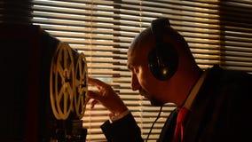 L'agent spécial secret écoute la conversation, enregistrant sur un à bobines merci banque de vidéos