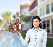 L'agente castana della proprietà presenta una nuova casa da vendere Fotografia Stock