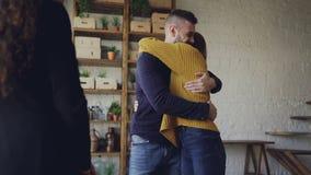 L'agente di alloggio sta fornendo le chiavi ai compratori di nuovo appartamento, il marito e la moglie felici sono abbraccianti e stock footage