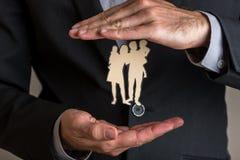 L'agente di assicurazione che fa il gesto proteggente intorno ad una carta ha tagliato il sil fotografia stock libera da diritti