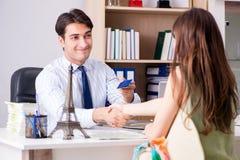 L'agente di viaggi maschio con il cliente nell'agenzia immagini stock