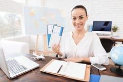 L'agente di viaggi tiene i biglietti per l'aereo nell'agenzia di viaggi Immagine Stock Libera da Diritti