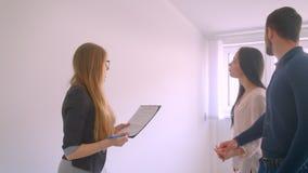 L'agente immobiliare caucasico femminile dimostra l'appartamento alle giovani coppie caucasiche che mostrano il piano ed i docume