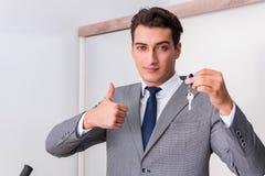 L'agente immobiliare con la chiave dalla nuova casa Immagine Stock