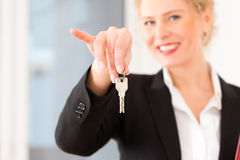 L'agente immobiliare giovane è con i tasti in un appartamento Fotografia Stock