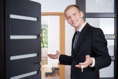 L'agente immobiliare invita i clienti ad osservare la casa fotografia stock libera da diritti