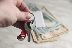 L'agente locativo del bene immobile, agente immobiliare tiene le chiavi all'appartamento nei dollari Il concetto dello scambio di immagini stock