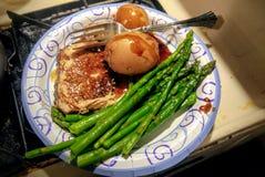 L'aglio ha lustrato la braciola di maiale con le patate novelle ed ha cotto a vapore le lance dell'asparago immagine stock libera da diritti