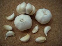 L'aglio intero e gli spicchi d'aglio sul sughero sorgono immagini stock libere da diritti