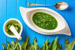 L'aglio selvaggio va con la minestra del mortaio, del cucchiaio e dell'aglio in piatto bianco su fondo di legno blu, lo stile di  Fotografia Stock Libera da Diritti