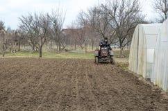 L'agricoltore è sul lavoro Il vecchio trattore ara il giacimento della molla per il giardino Fotografie Stock Libere da Diritti