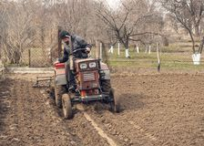 L'agricoltore è sul lavoro Un vecchio trattore e un campo arato Fotografie Stock