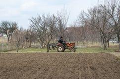 L'agricoltore è sul lavoro Vecchio trattore fra gli alberi da frutto Immagini Stock Libere da Diritti
