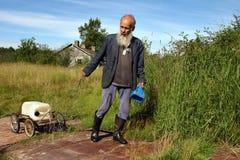 L'agricoltore agricolo dell'uomo anziano e grigio-barbuto tira il carretto con caniste Immagini Stock